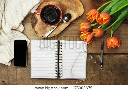 Overhead of an open book cell phone coffee and flowers over a wood table top ready to plan an agenda. Flat lay top view style.
