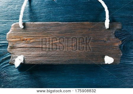 Brown textured wood signboard without text on black wood surface. Top view