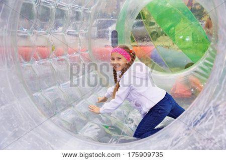 The joyful girl moves inside the zorb