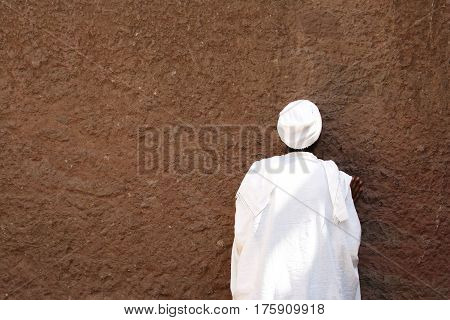 The praying Orthodoxy pilgrim in front of  Lalibela Rock Church