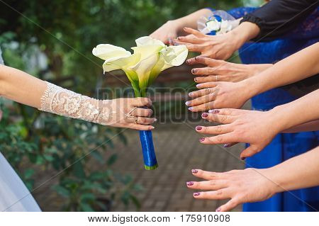 hands of bridesmaids are drawn to a wedding bouquet of callas.