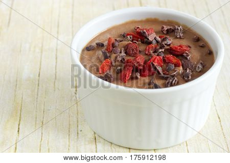 Photo of healthy pudding made from the cauliflower. Dessert with cocoa nibs and goji berries.