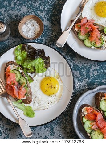 Fried egg and salmon cream cheese sandwich - delicious breakfast brunch or snack. On wooden background top view. Flat lay