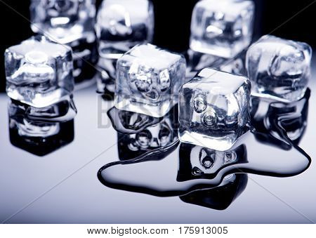Ice cubes with water on a dark background
