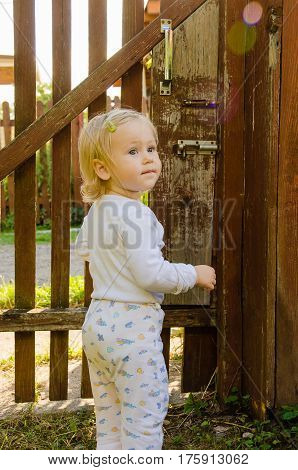 Little girl in front of a closed gate summer cottage