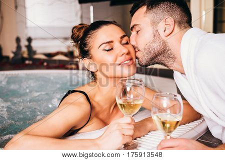 Beautiful Young Couple Relaxing Together And Drinking White Wine In Spa