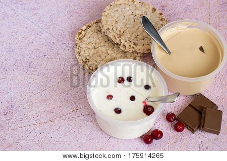 Curd dessert with cranberries and milk chocolate in plastic jars and dietary crispbread on an old table.