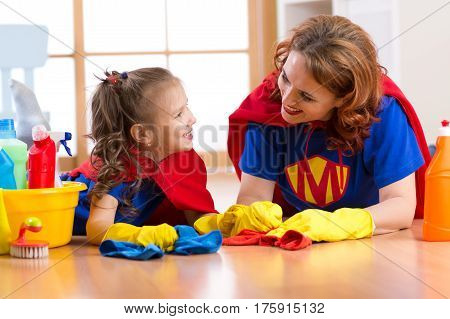 Beautiful mother and her cute kid daughter dressed like superheroes. Woman and child ready to cleaning the house.