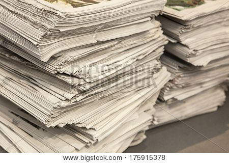 Two huge pile of many newspapers over floor