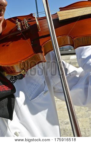 A violinist in a long sleeve white shirt runs the bow across the strings of a violin.