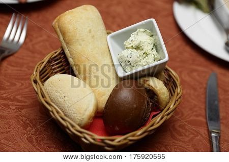 Basket with various bread and butter on a table