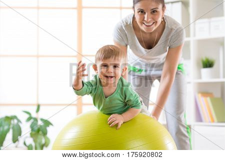 Happy mother and baby boy on fitness ball in nursery at home. Gimnastics for kids on fitball.