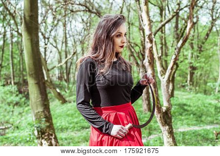 mysterious woman with a sickle in spring forest