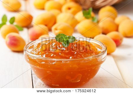 Apricot jam in a glass bowl fresh apricots on wooden background