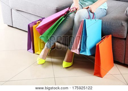 Female Legs With Yellow High Heels And Shopping Bags On Grey Sofa