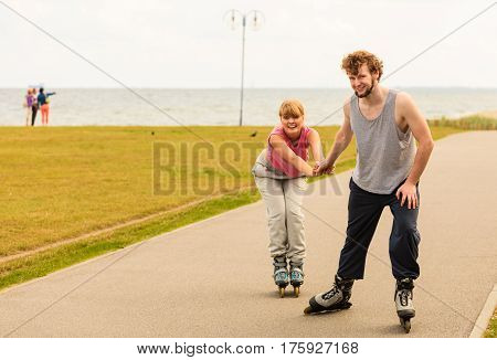 Active holidays exercises relationship concept. Young man dressed in sports clothes putting his girlfriend up to do inline skating while holding her hand on promenade