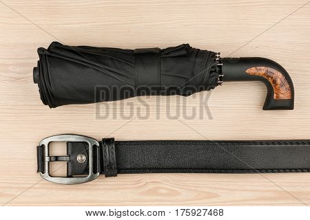 Umbrella and genuine leather strap lie on a wooden surface top view
