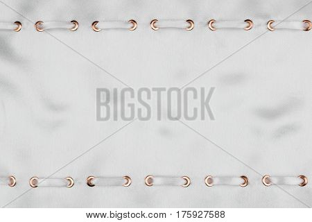 White satin ribbon inserted in the gold rings on white silk trendy background. With space for text