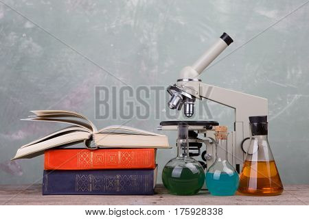 Chemical Flasks, Books And Microscope On The Desk On Green Background