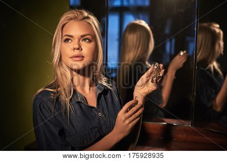 Young blonde beautiful woman wear perfume in retro bottle of perfume in console-mirror