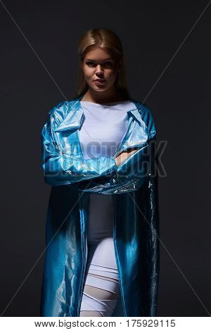 Young blonde woman in white leggings sneakers shoes and fashion turquoise splendid cloak