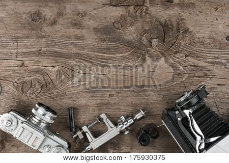 Old cameras and a tripod lie on a wooden surface. View from above