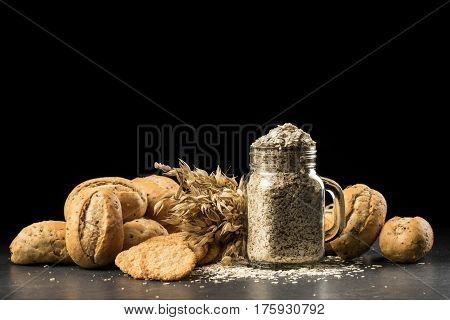Oat bunch baked white bread cookies and flakes in flavouring jar isolated on black background. Grain bouquet golden oats spikelets on dark wooden table buns and can filled with dried grains. Food bakery concept