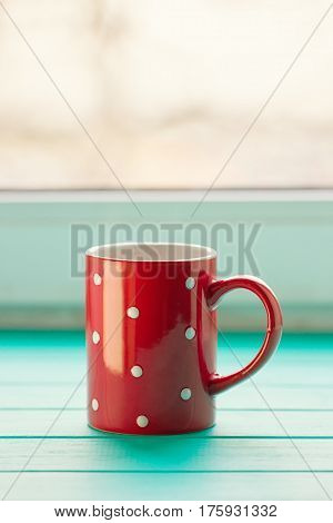 Red cup in white peas on a windowsill