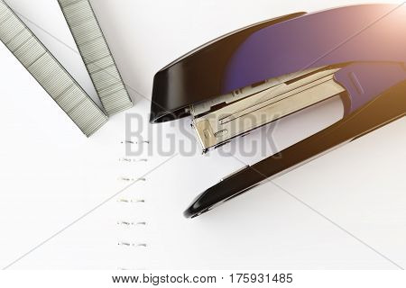 Stapler with staples on white paper. Staples in paper close-up. Office equipment concept.