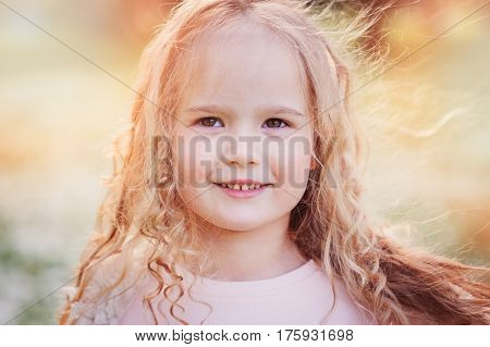 spring portrait of beautiful dreamy curly 5 years old child girl walking in blooming garden