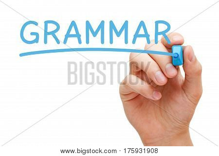 Hand writing Grammar with blue marker on transparent glass board.