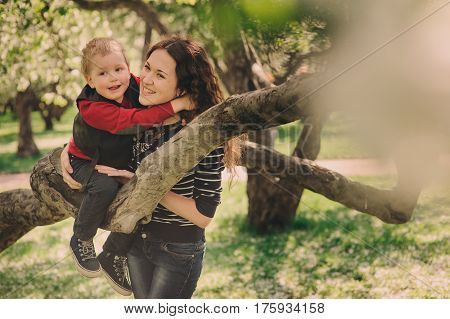 happy young mother and toddler son walking together outdoor and playing candid lifestyle shot