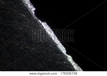 Cold steel razor blade by microscope. Microscopic scratched steel surface
