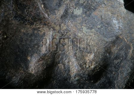 Background texture corroded metal of ancient Greek copper coin. Rough grained surface super macro close-up by microscope