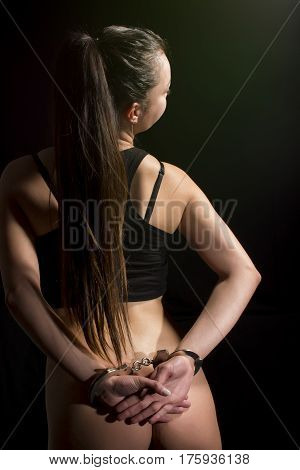Hand cuffed woman isolated on  black background