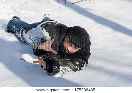 Old man is asking for the help after falling down on slippery snow in bright winter day.