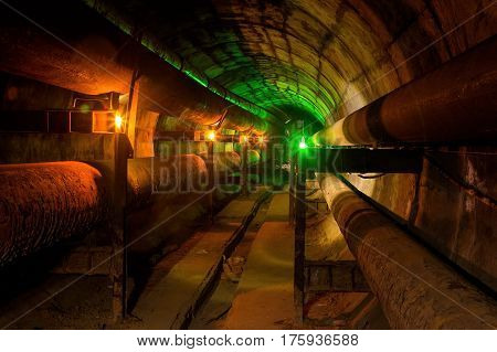 Dirty tunnel of heating duct with rusty pipeline illuminated by candles and green lantern