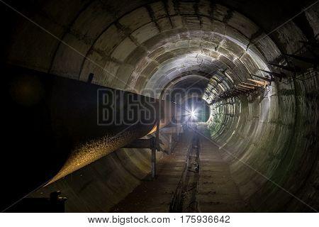 Old round dirty underground technical tunnel with rusty pipeline under Voronezh