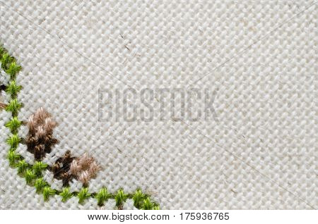 Handmade Embroidery by Cross Stitch in the View of Acorns. Texture of Beige Natural Linen Fabric with Embroidery for Background.
