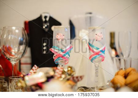 Two beautiful wedding glasses on the background of the wedding table close up