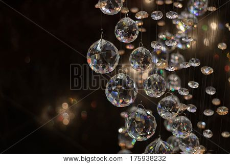 Beautiful crystal balls hanging on fine threads beautifully reflect. Cristall sphere in the dark