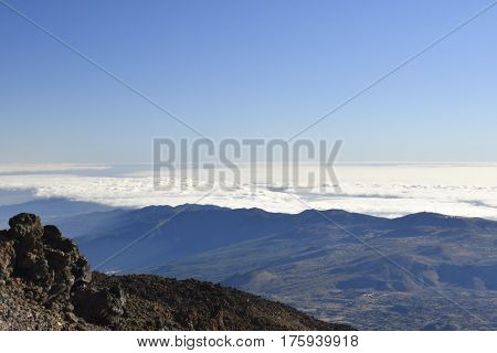 View from Teide to the North over Tenerife Island with lava stone in foreground and blue sky and clouds in background picture from Tenerife Spain.