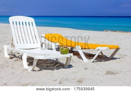 two chaise-lounges on the beach of the Caribbean sea