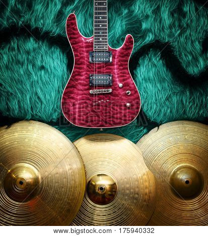 Purple electric guitar with three cymbals on turquoise color faux fur wall. Musical instruments background