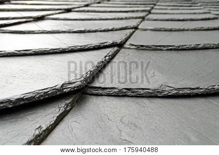 Wet slate slabs stacked on top of a roof