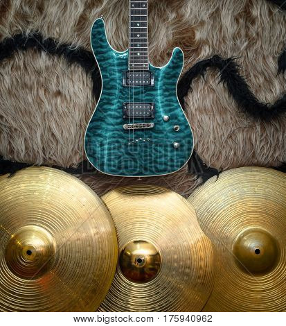 Electric guitar with three cymbals on faux fur wall. Musical instruments background