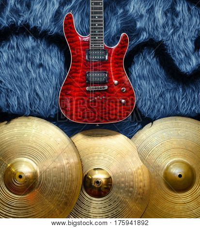 Red Electric guitar with three cymbals on blue faux fur wall. Musical instruments background
