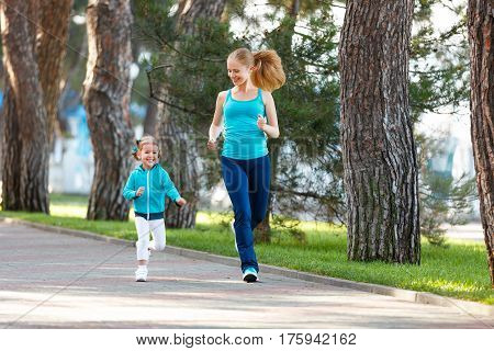 sport family. Mother and baby daughter jogging run on nature in summer