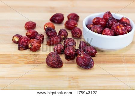 Fruit rosehip isolated on a wood background.