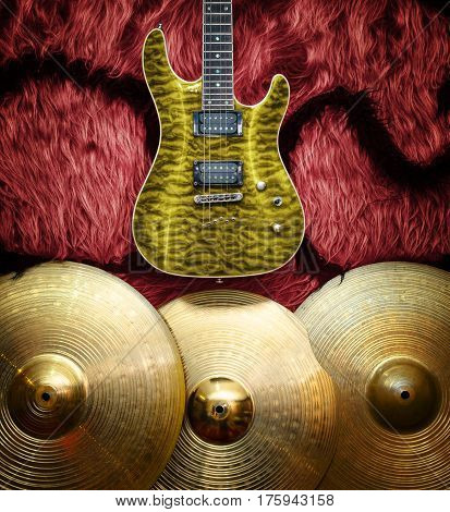 Yellow electric guitar with three cymbals on faux fur wall. Musical instruments background